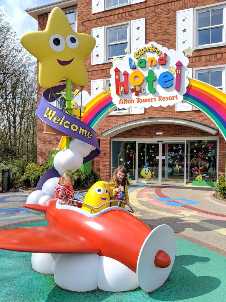 two children in a toy plane in front of the CBeebies Land Hotel